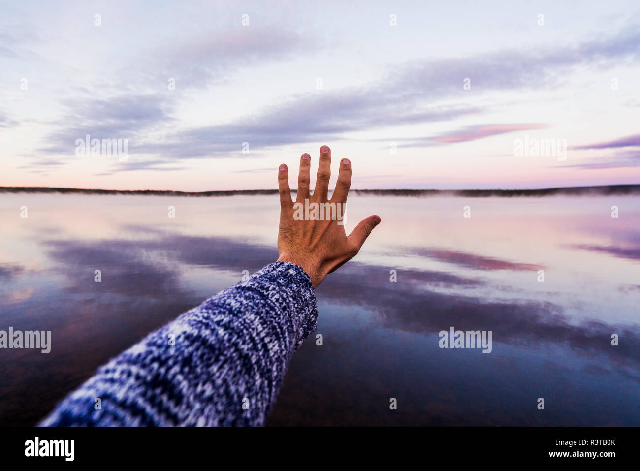 Hand of young man reaching out to the sky - Stock Image