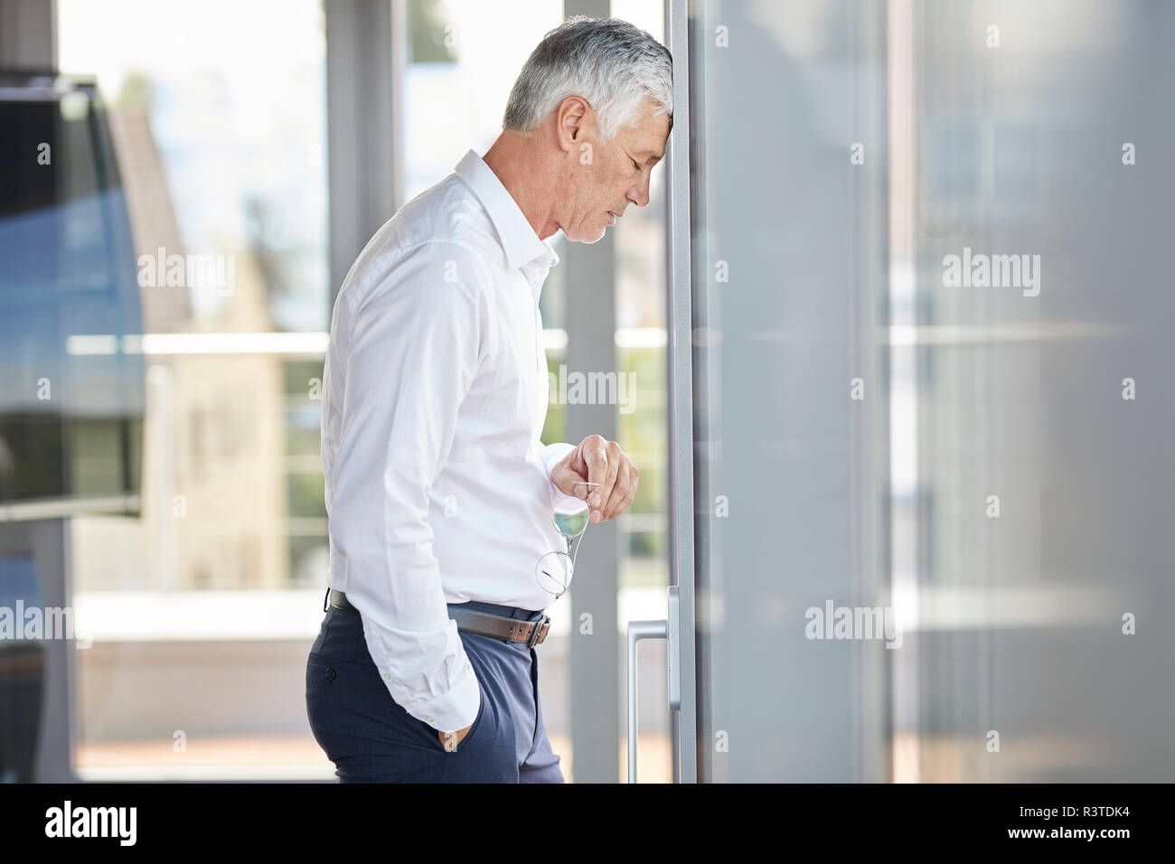 Exhausted businessman resting head on windowpane - Stock Image