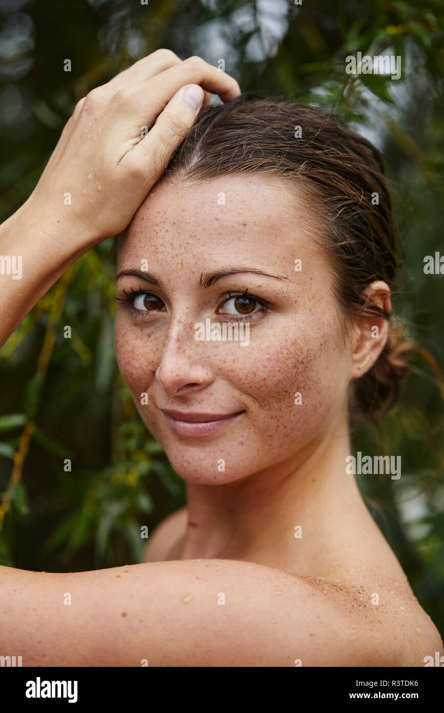Portrait of freckled young woman in nature - Stock Image