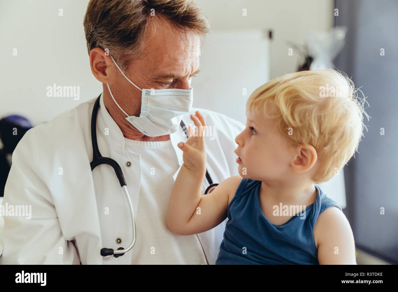 Protective Wearing Pediatrician Sitting On Lap Of Mask Toddler