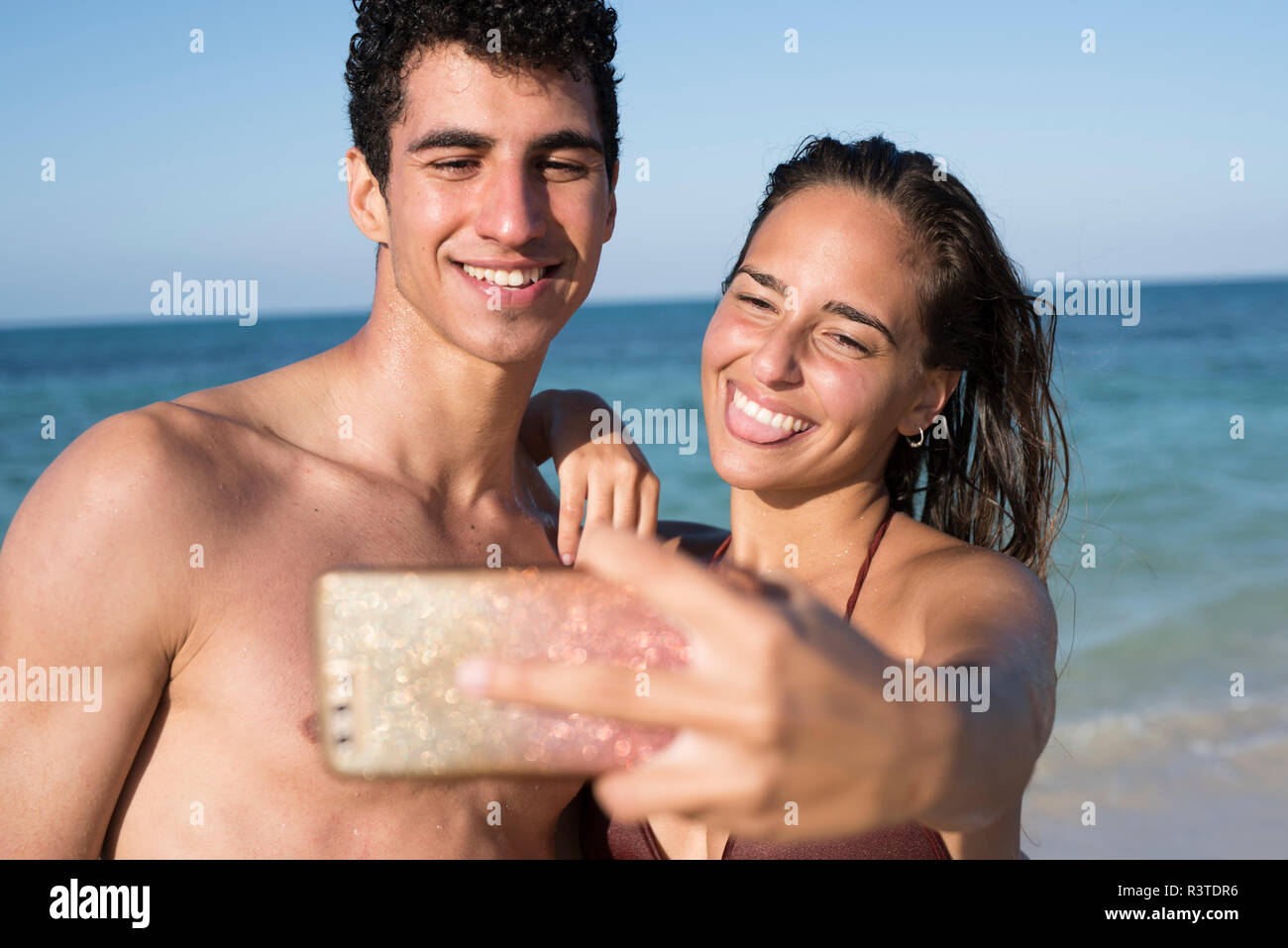 Happy young couple taking selfies on the beach - Stock Image
