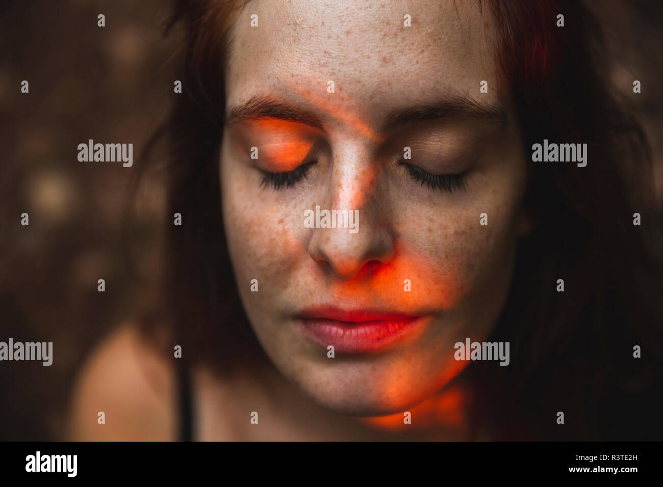 Portrait of young woman with freckles closing her eyes Stock Photo