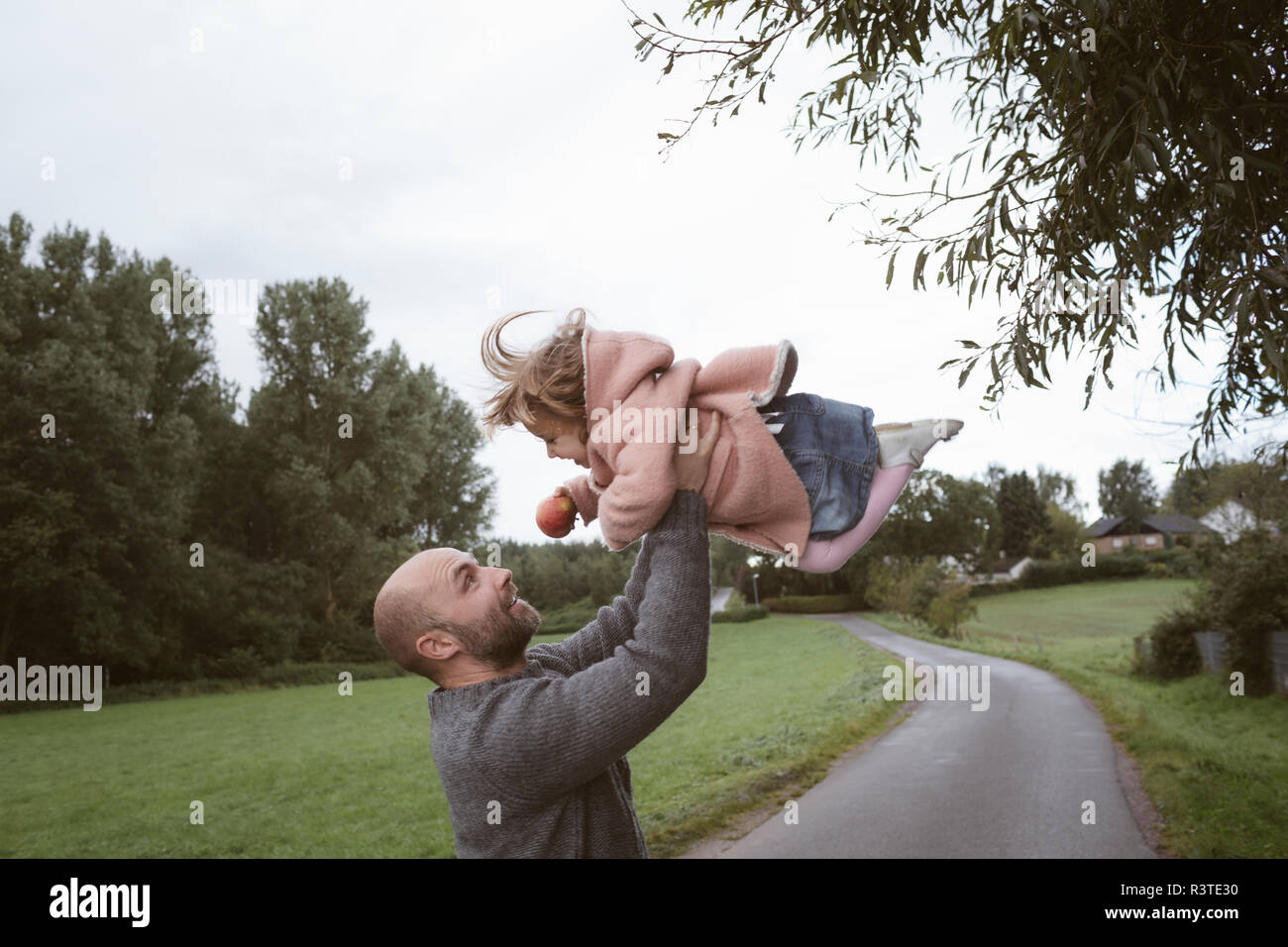 Father holding little daughter aloft - Stock Image