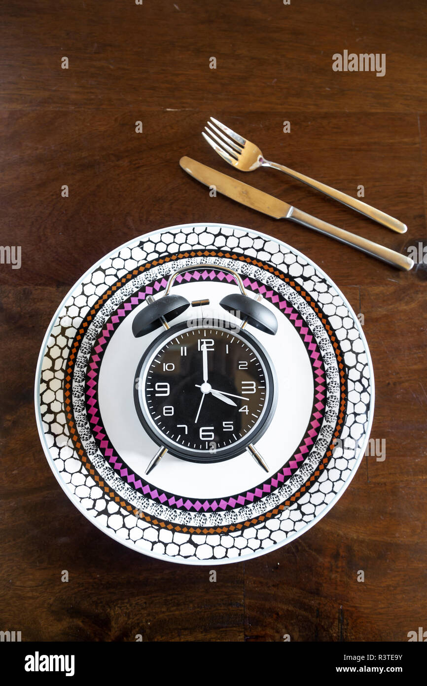 Intermittent fasting, trend 16:8 fasten, alarm clock on plate - Stock Image
