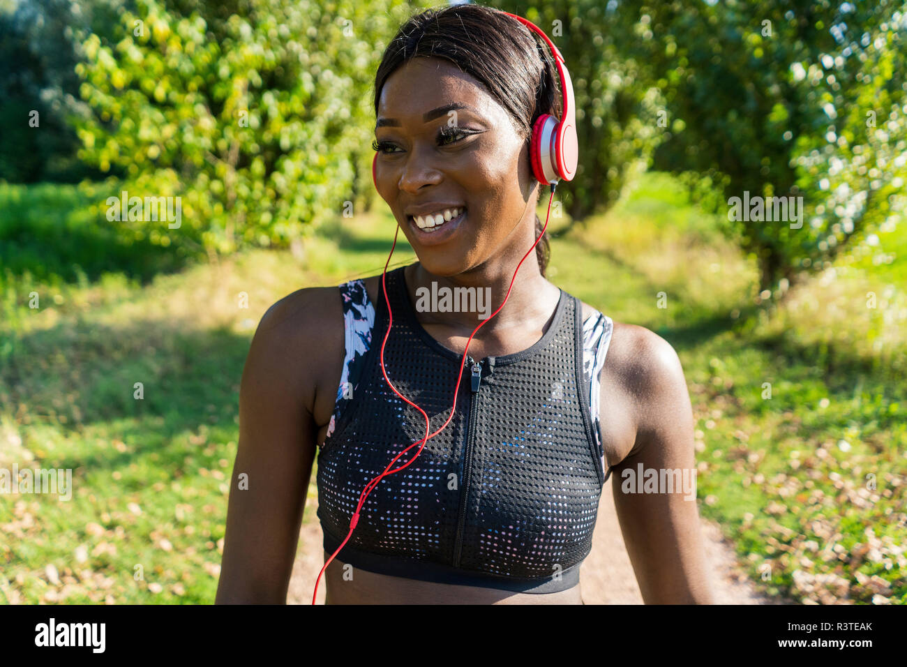 Young athlete in nature, listening music with headphones - Stock Image