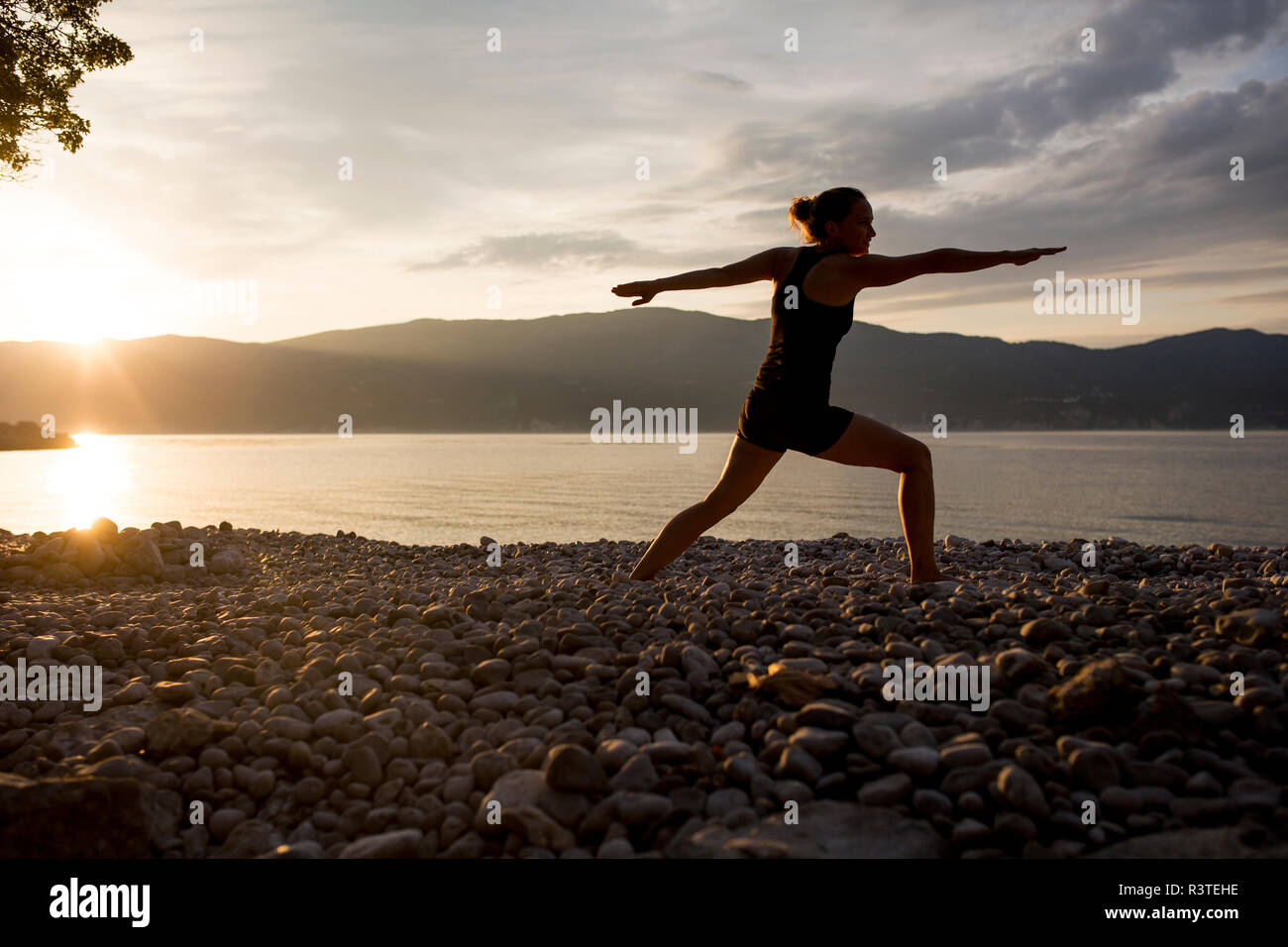 Young woman doing yoga at the stony beach at sunset, Warrior pose - Stock Image
