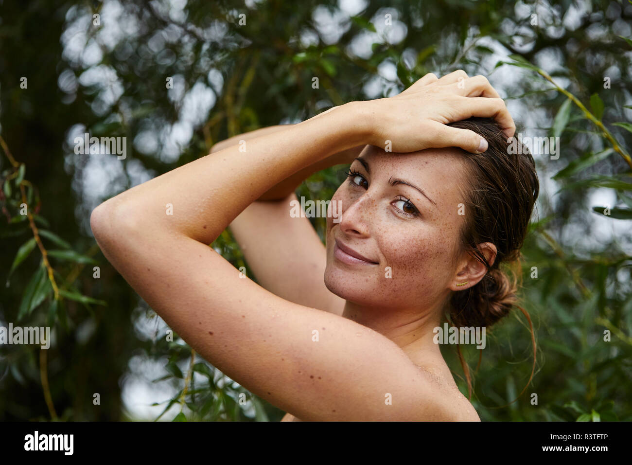 Portrait of freckled young woman in nature Stock Photo