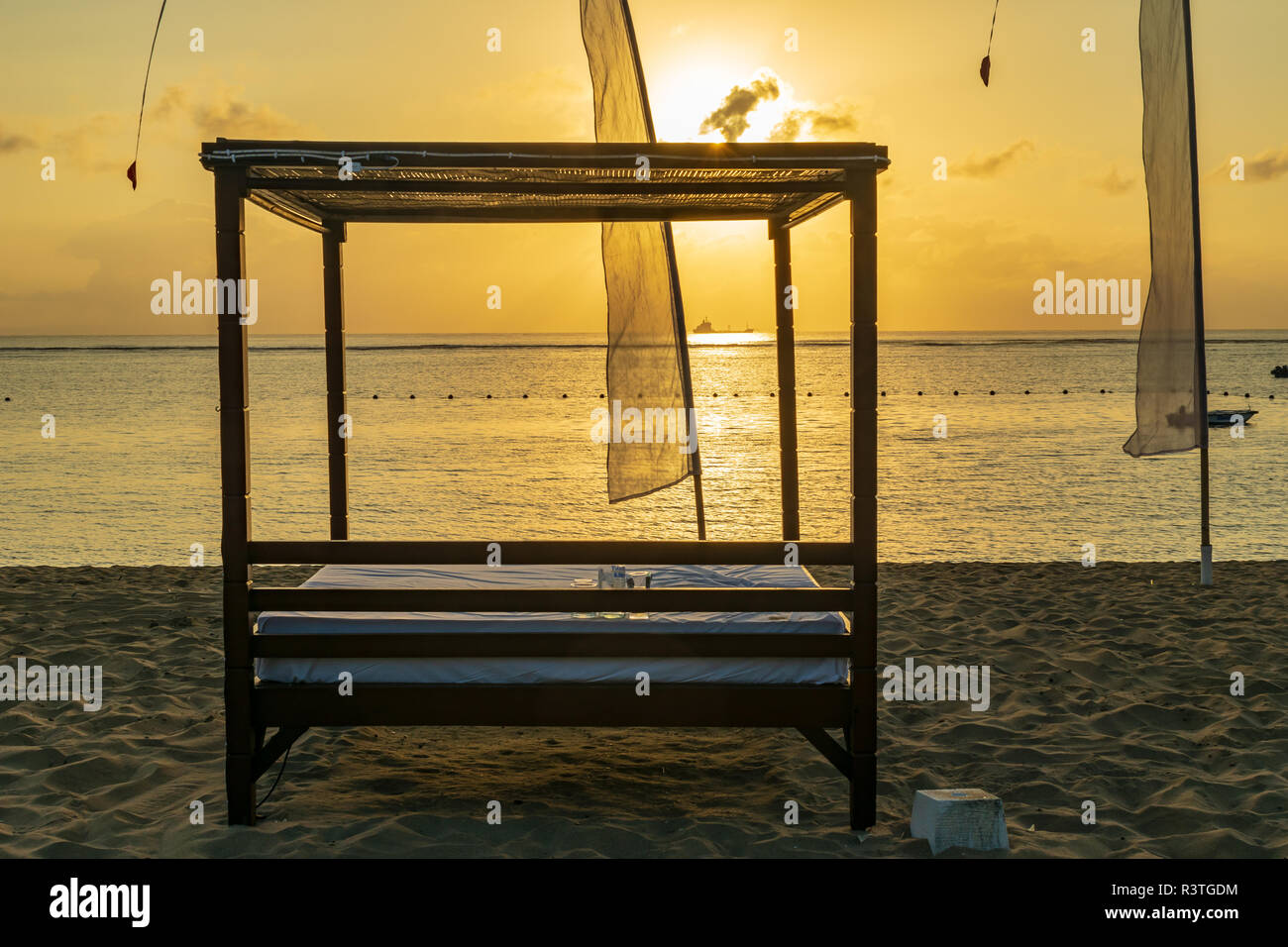 sunrise in Nusa Dua beach, a cot to sleep by the sea/ beach, with the rays of the rising sun to wake you up, beautiful Bali - Stock Image