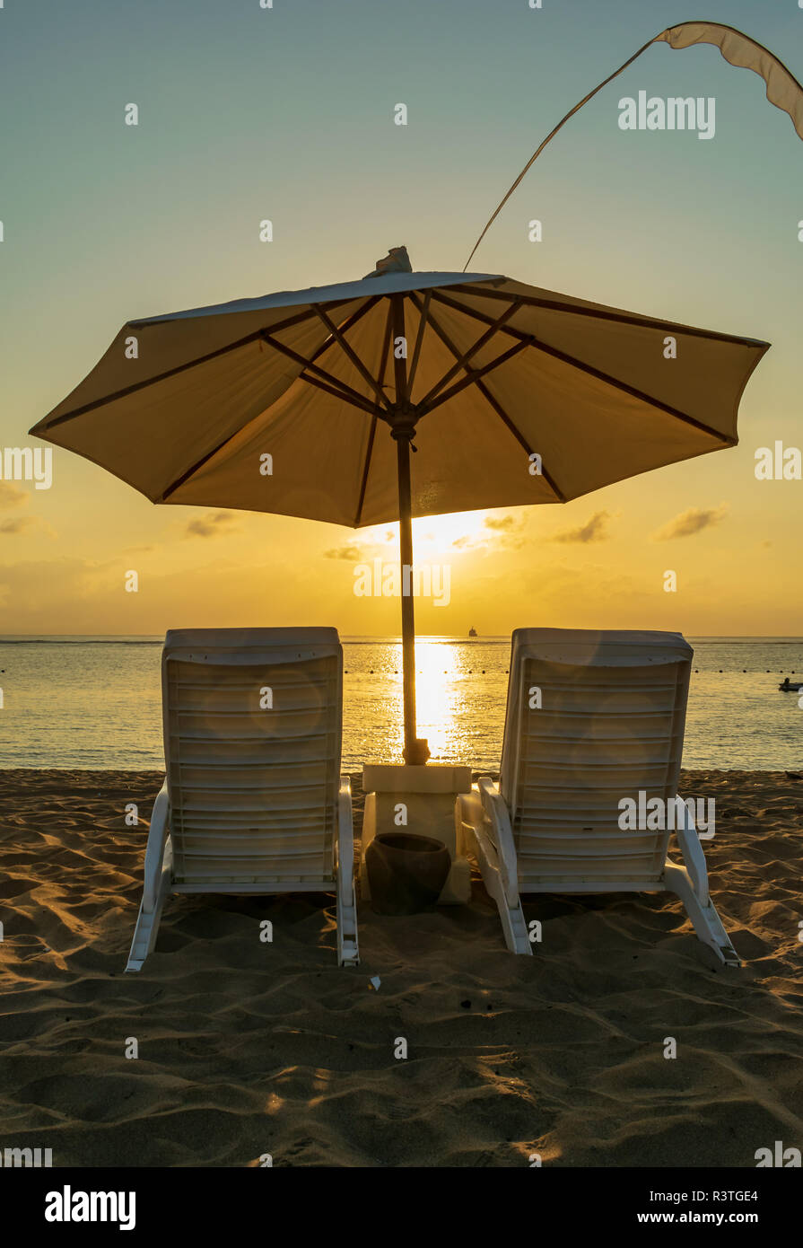 sunrise in Nusa Dua beach, a pair of white chaise lounges and a parasol / umbrella to enjoy the beautiful sunrise, beautiful Bali - Stock Image