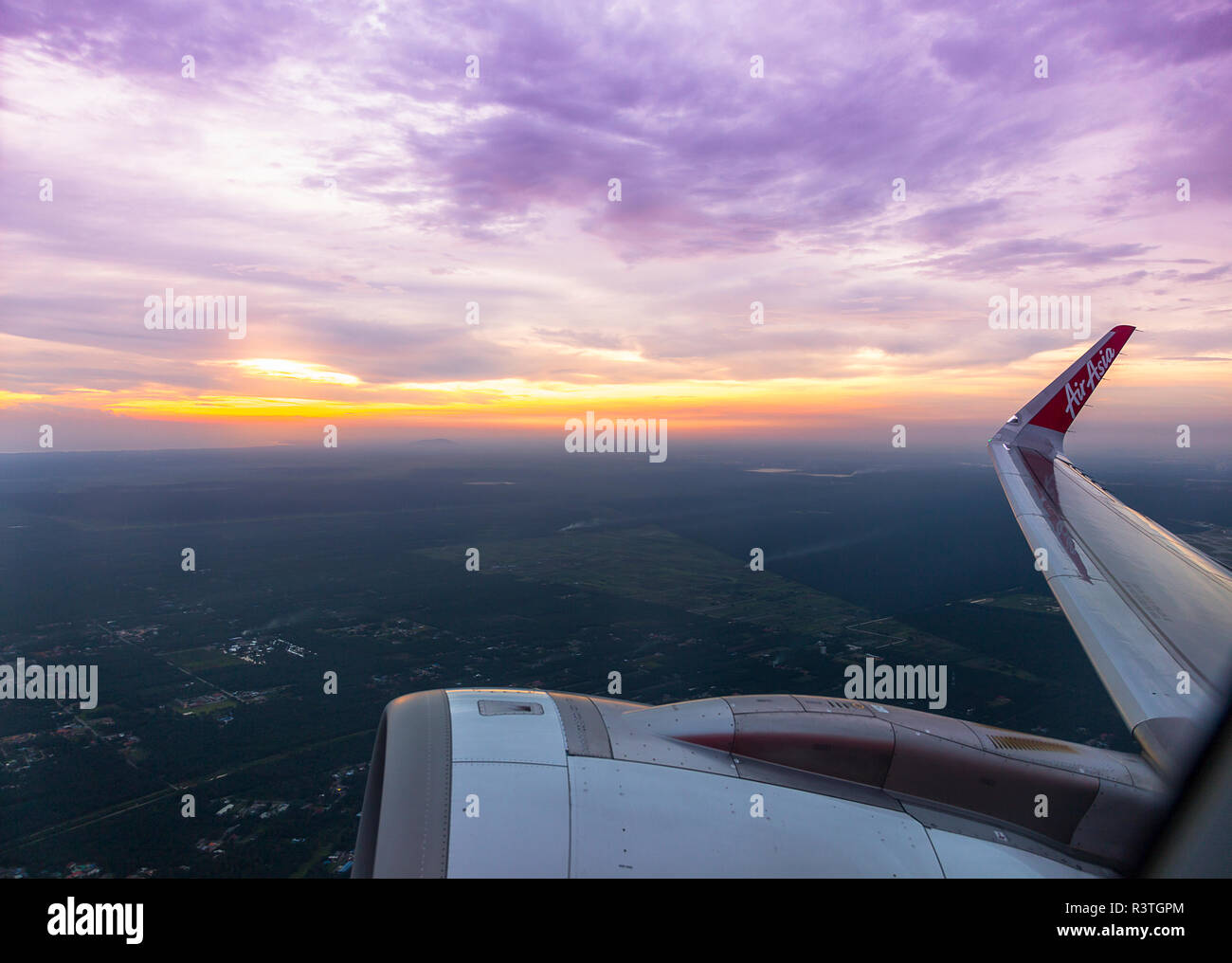 Looking out the window of a commercial airliner with the engine and wing and a purple yellow sky and sun. - Stock Image