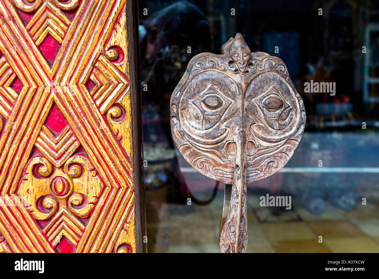 Orange and gold wood frame with a wooden carved owl handle. - Stock Image