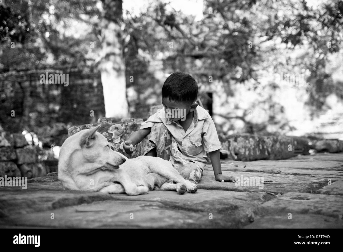 Siem Reap, Cambodia - September 12, 2010: Cambodian boy near some ruins playing with his dog. - Stock Image