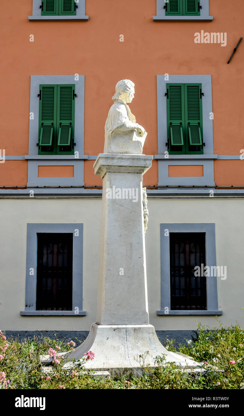 Classical marble statue on a plinth against a colourful salmon-coloured wall in Fivizzano, Tuscany, Italy. Stock Photo