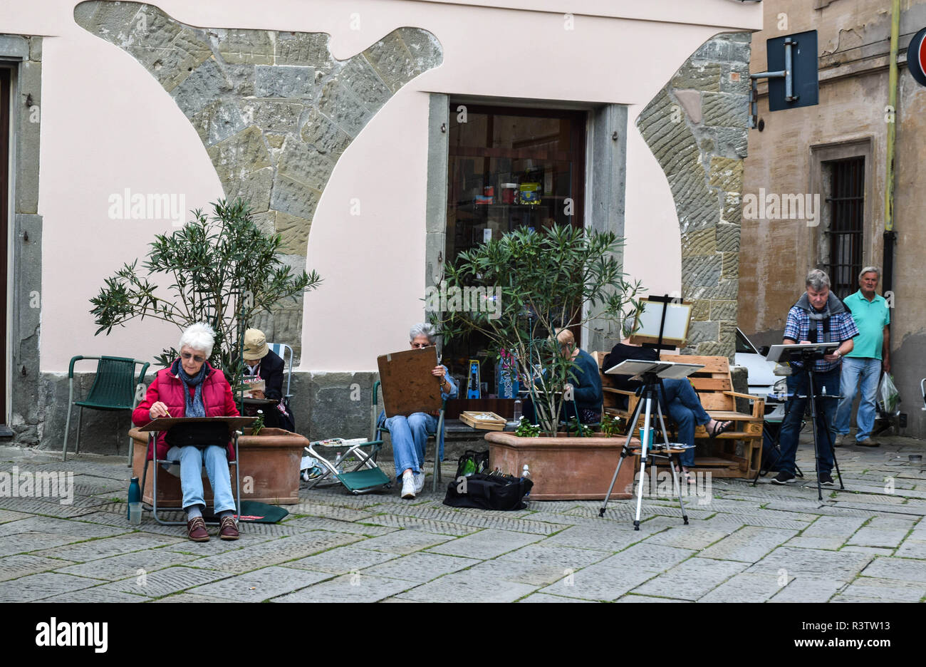 Participants of a British painting course in the central piazza on market day in Fivizzano, Tuscany, Italy.. - Stock Image