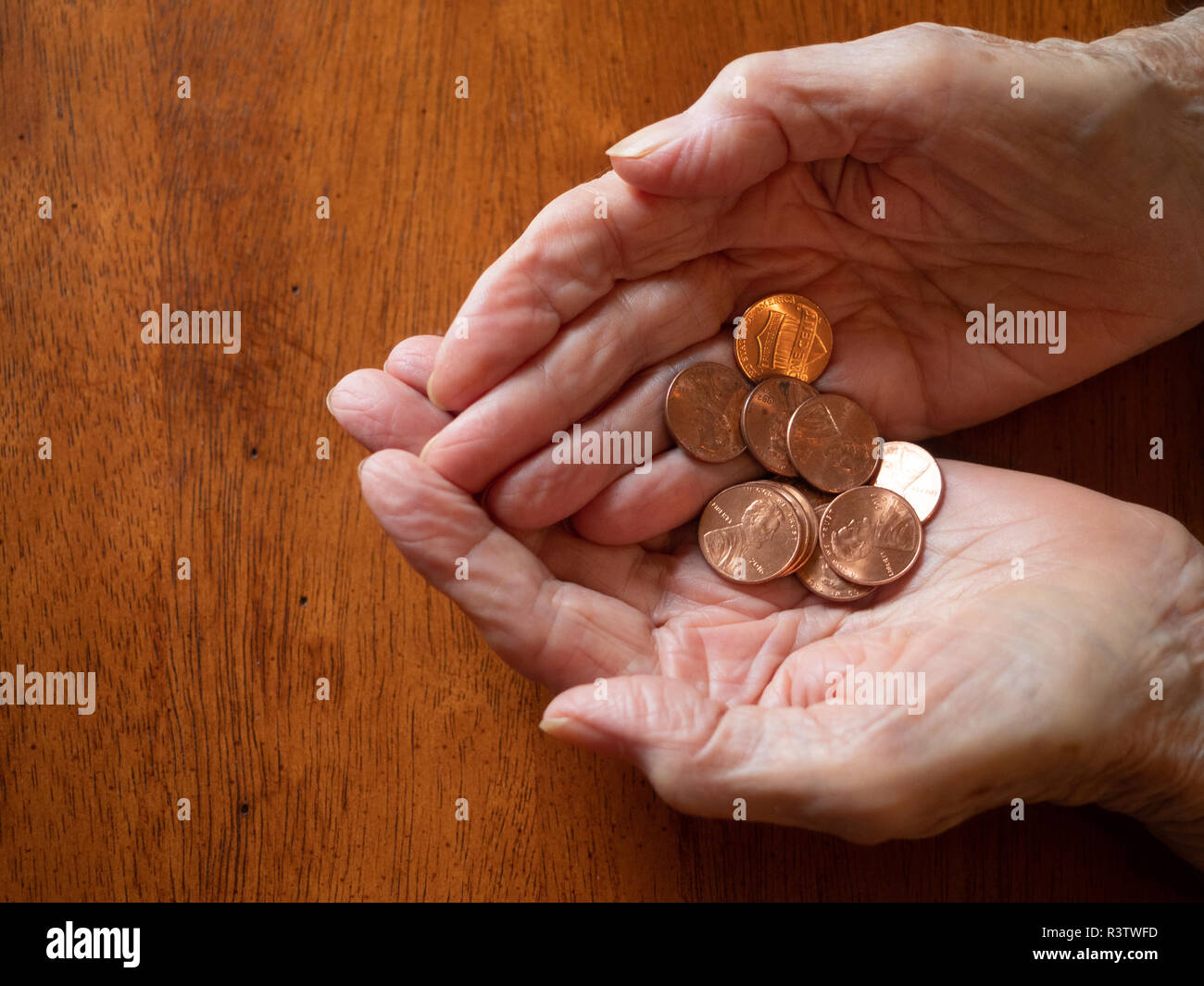 Close up of elderly woman's hands holding pennies. Photographed from above with a wooden table in the background and copy space. - Stock Image