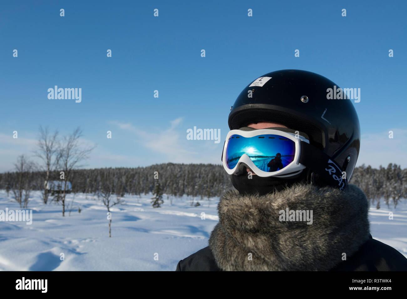 Tourist wearing helmet for snowmobile driving, Jukkasjarvi, Sweden. - Stock Image