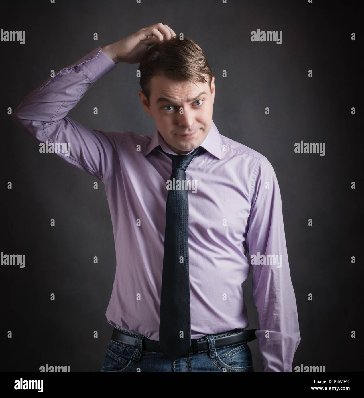 5eb57ffc Portrait of pensive young man in pink shirt and dark tie, against dark  background.