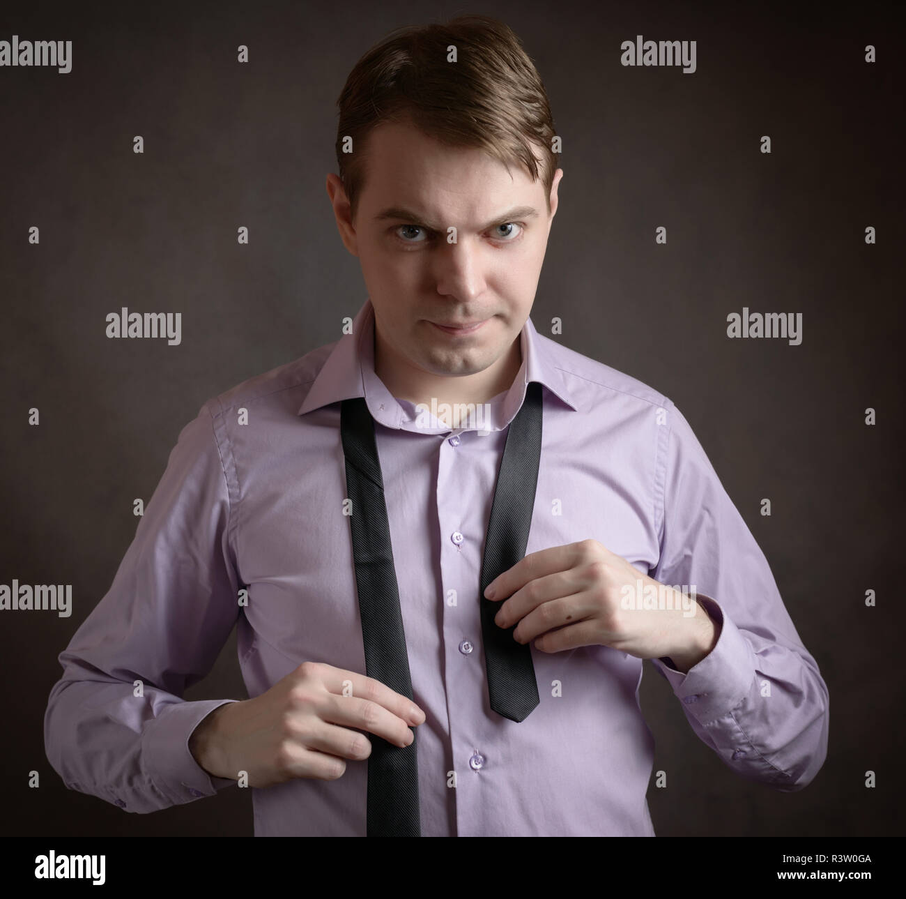 6521fe5b Young man in pink shirt tying the necktie Stock Photo: 226128010 - Alamy