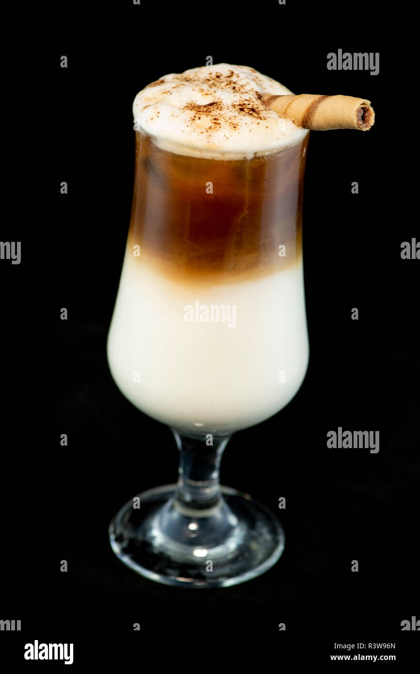 Alcoholic coffee cocktail with coffee liqueur, fresh cream and milk with isolated black background Stock Photo