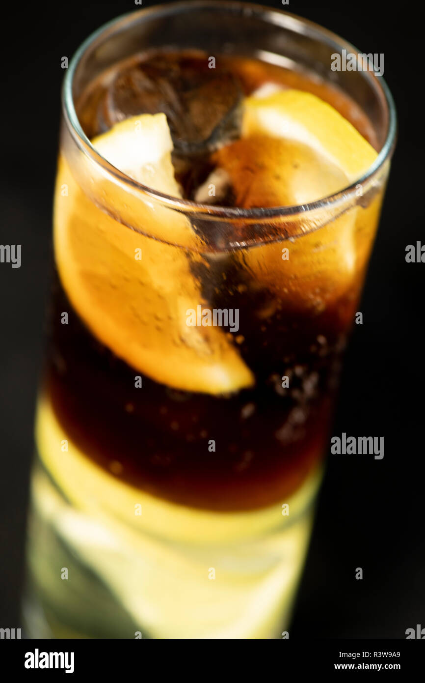 Cuba Libre cocktail with rum, coke and lime juice with lime wedge and full of ices with isolated black background - Stock Image