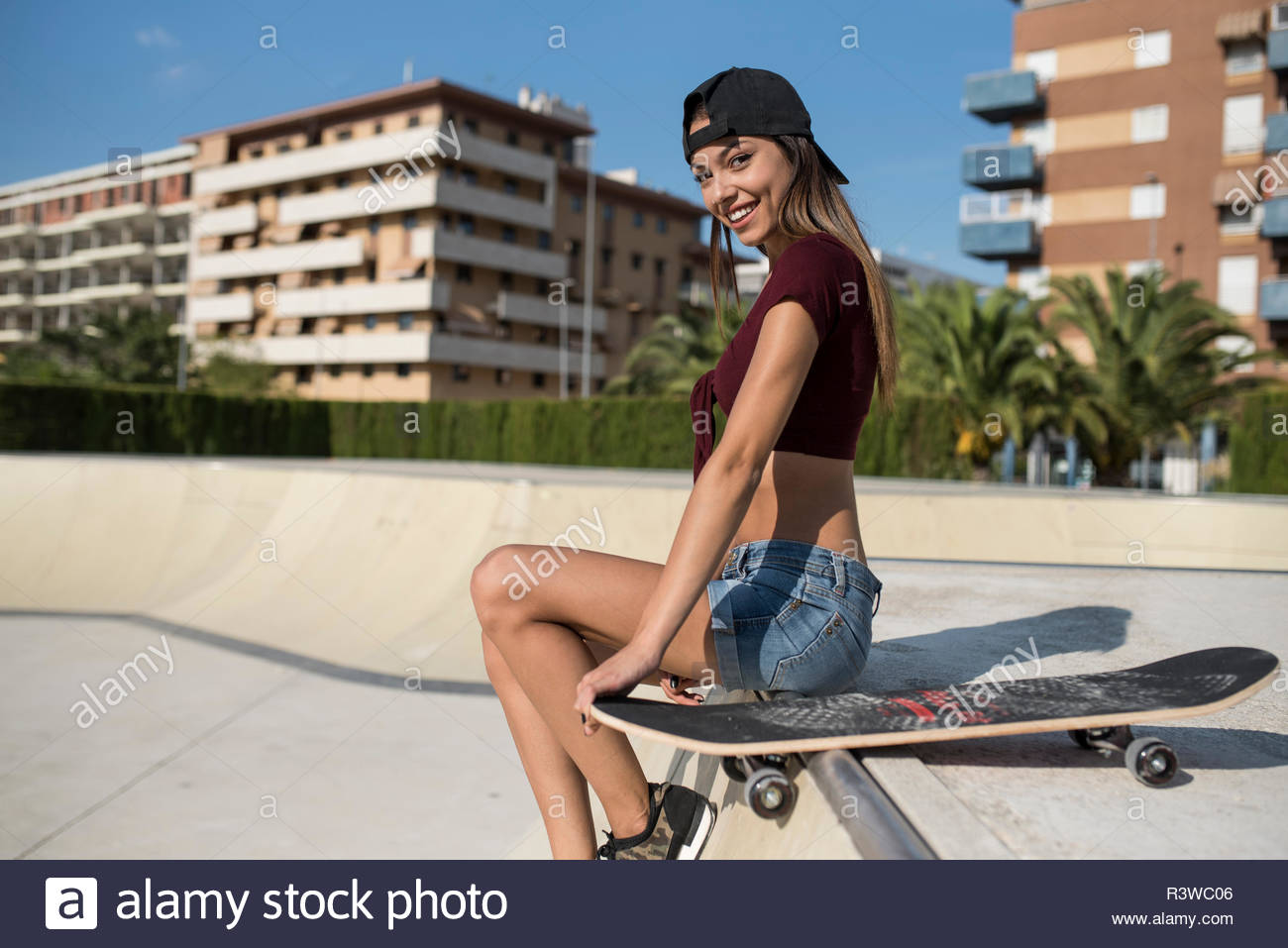 Young pretty woman sitting on wall of skatepark - Stock Image