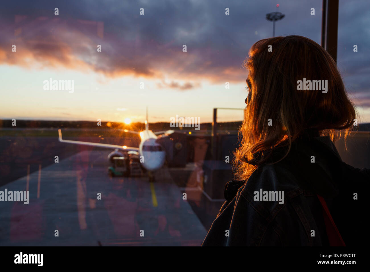 Young woman looking through window on plane at the airport at sunset - Stock Image