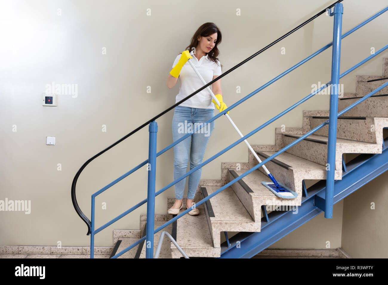 Young Female Janitor Cleaning Staircase With Mop - Stock Image