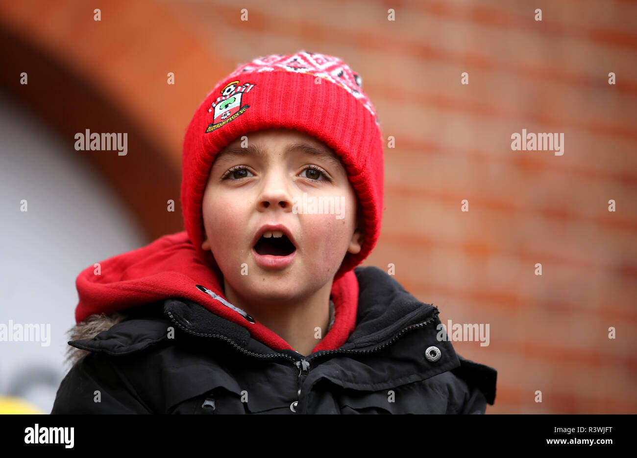 Southampton fan outside the ground before the Premier League match at Craven Cottage, London. - Stock Image