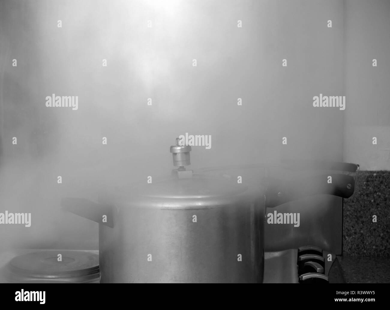 Pressure cooker on the stove releasing steam, black and white photography - Stock Image