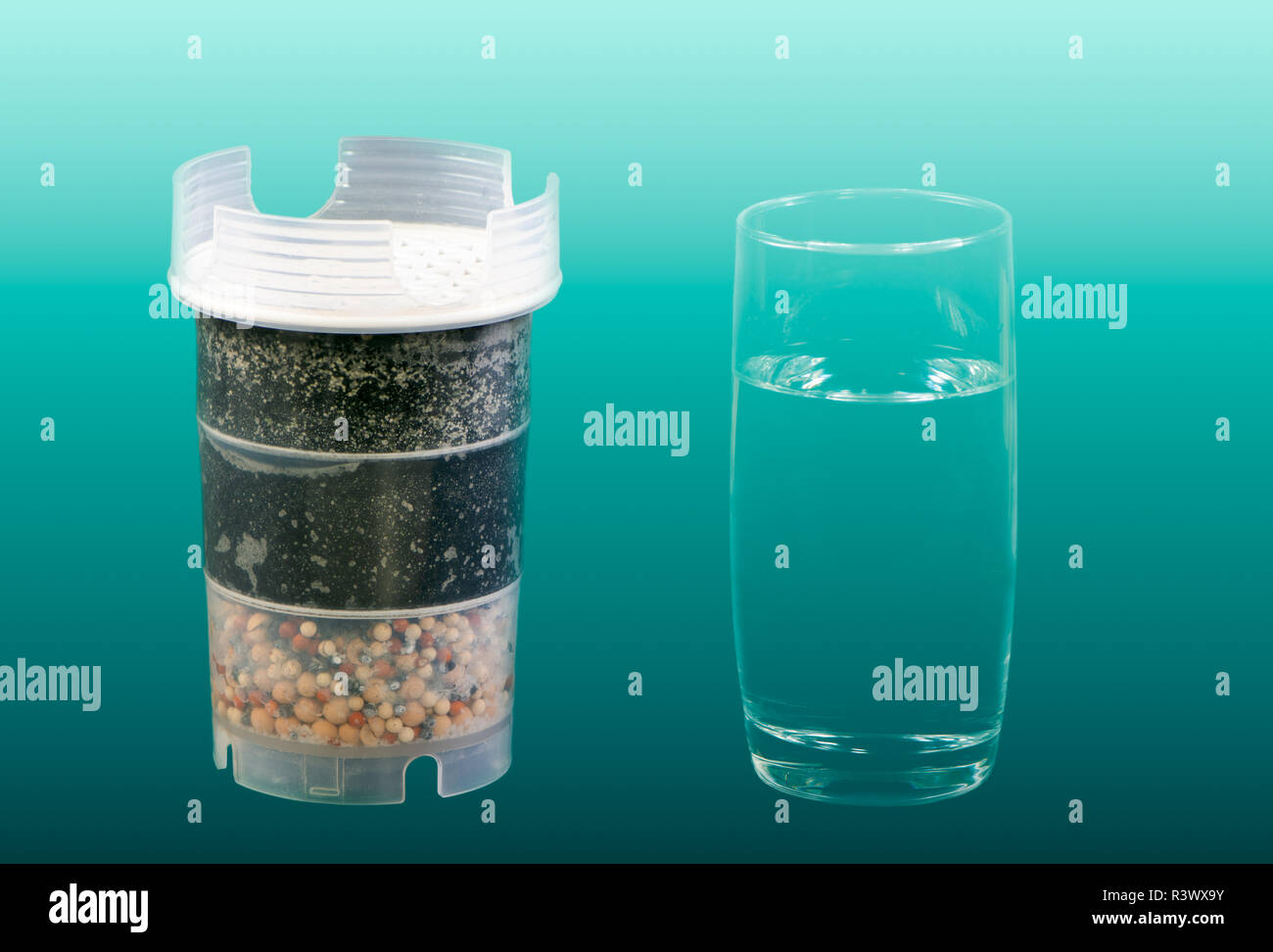 Water purification filter with active carbon and a glass of fresh and clean drinkable water - Stock Image
