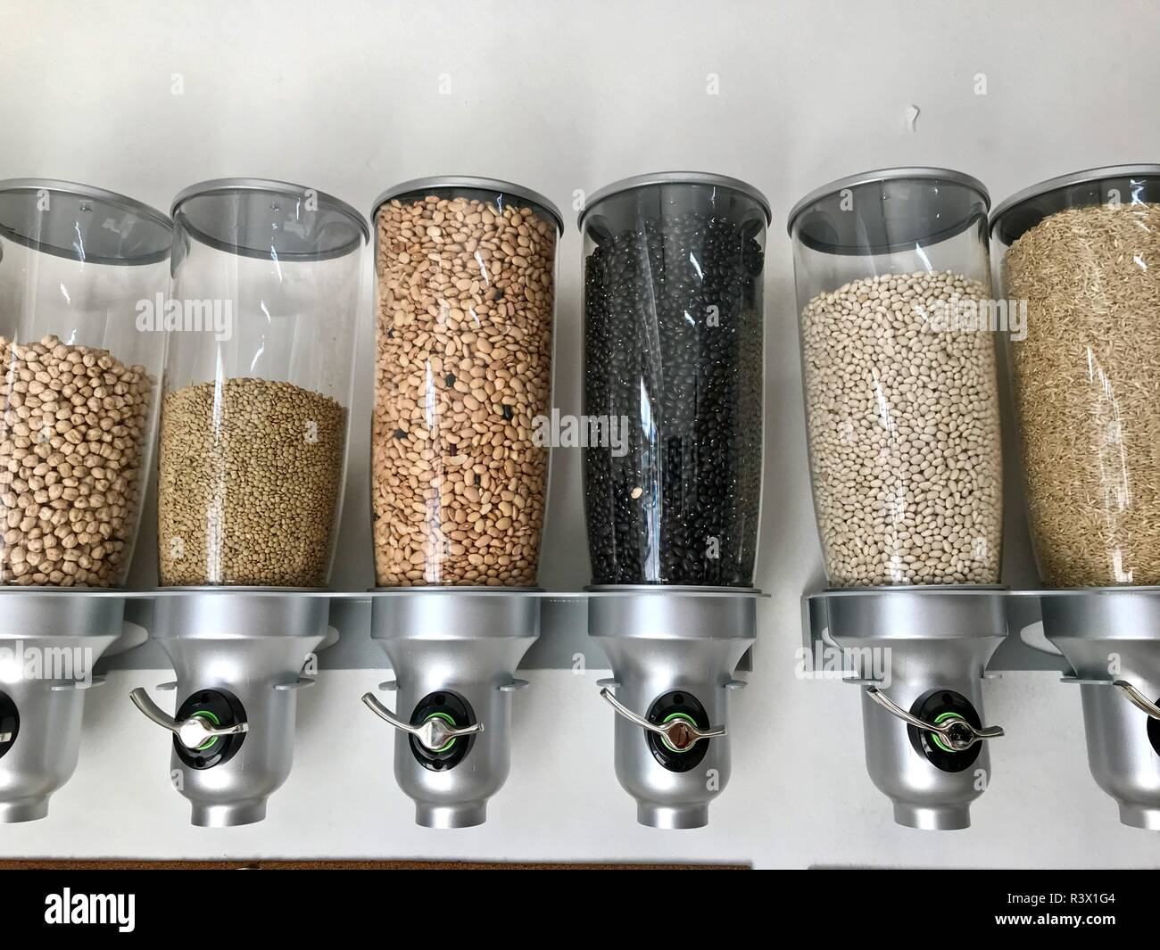 Wall mounted containers at a zero waste store full of lentils, beans, chickpeas and rice where you can refill your own containers. - Stock Image