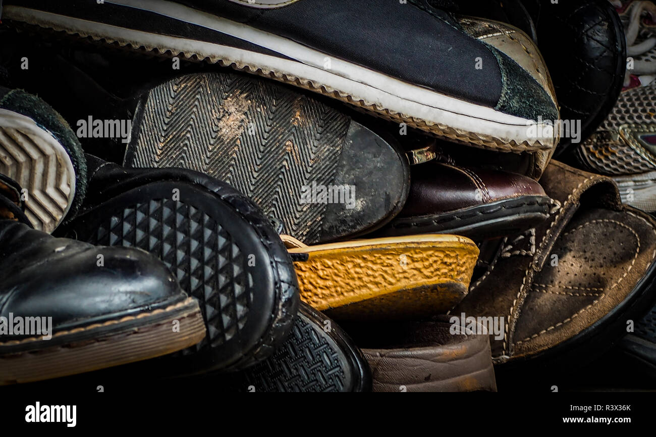 Close up of old dirty male shoes. Used shoes. Heap of old shoes. Many of dirty men shoe. Men shoes collection with not organized. Men keep shoe with d - Stock Image