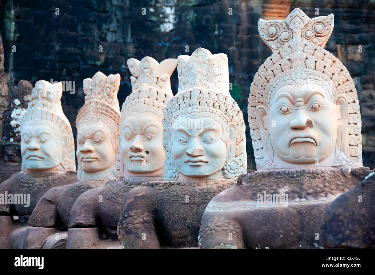 Stone figures line a causeway leading to Angkor Thom showing the 'demons' who wear military headdress - Siem Reap, Cambodia, South East Asia - Stock Image
