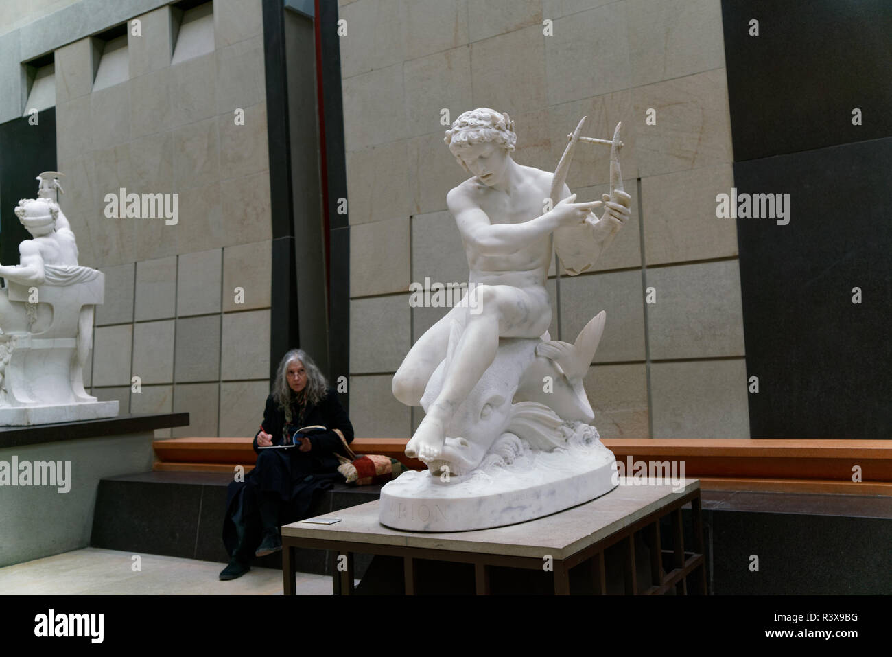 """A woman in the Musée d'Orsay in Paris sketching """"Arion seated on a Dolphin,"""" a sculpture by Ernest Eugene Hiolle that dates from 1870. - Stock Image"""