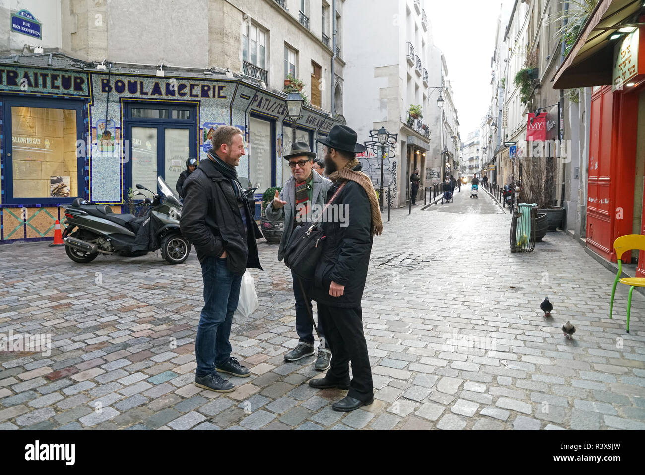 Men conversing on the ancient rue des Ecouffes in the Marais district of Paris. The street dates from the 13th century. - Stock Image