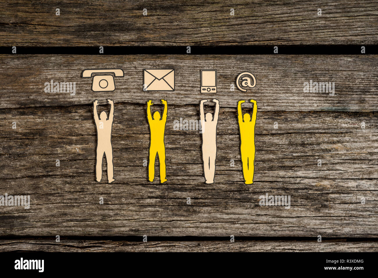 Teamwork and customer service concept with cut outs of four men supporting a line of phone, web and mail icons from below over a rustic background. - Stock Image