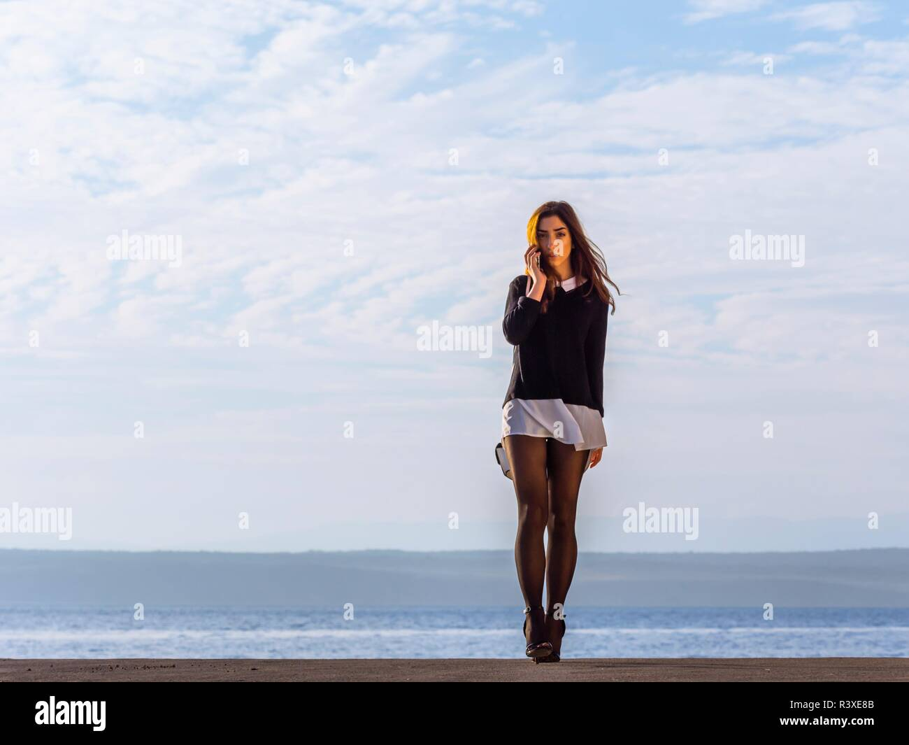 Attractive teen girl adolescent walking towards camera serious talking on mobile phone cellphone isolated against sunlit sky Black tights Stock Photo