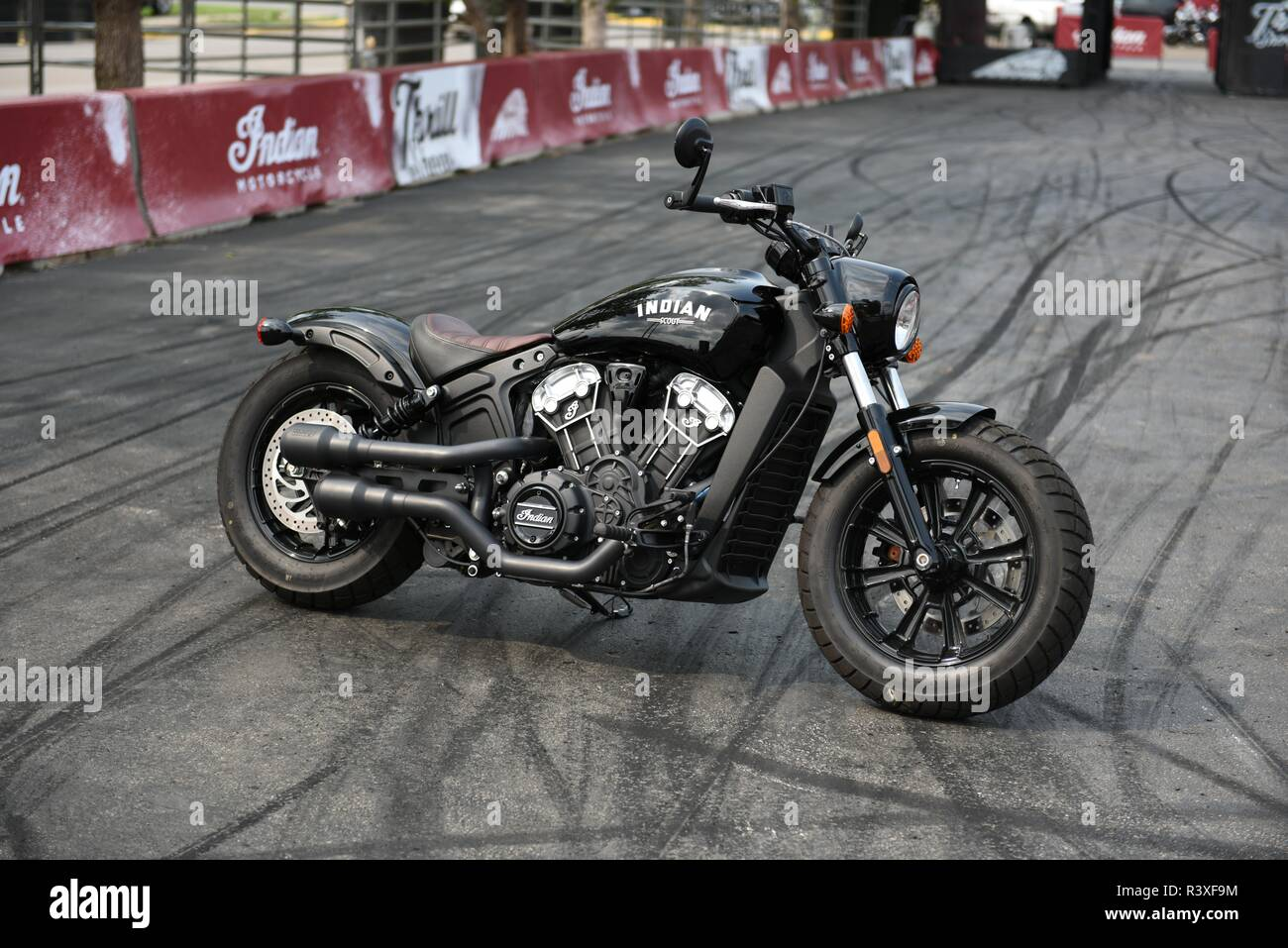 American made Indian Scout motorcycle on an exhibition track with a background of rubber tire burnout marks. - Stock Image