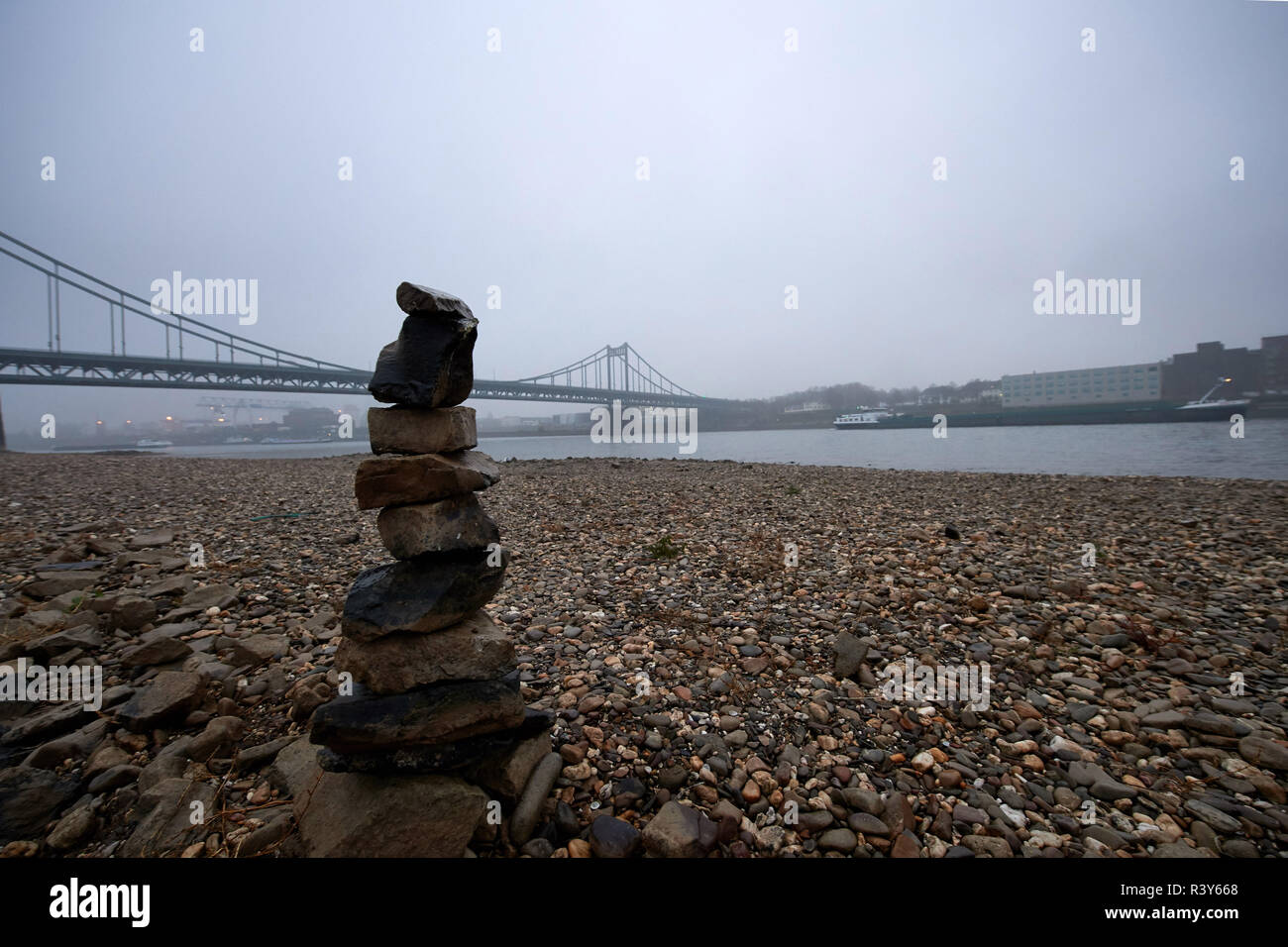 Duisburg, Germany. 24th Nov, 2018. A small stone tower stands in the riverbed of the Rhine between Duisburg and Krefeld-Uerdingen. After isolated rainfalls had provided the Rhine with some water, the water level is now falling again according to the Duisburg-Rhine Waterways and Shipping Authority. Credit: Bernd Thissen/dpa/Alamy Live News - Stock Image