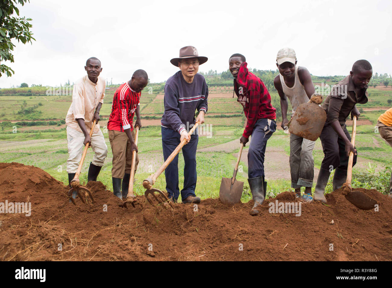 """(181124) -- KAMONYI (RWANDA), Nov. 24, 2018 (Xinhua) -- Chinese Ambassador to Rwanda Rao Hongwei (3rd L) participates in monthly community work, Umuganda, in Kamonyi district, central Rwanda, on Nov. 24, 2018. Diplomatic missions in Rwanda and Rwandan Ministry of Foreign Affairs and International Cooperation on Saturday organized a diplomatic Umuganda in Kamonyi. Taking root from Rwandan culture of self-help and cooperation, Umuganda, held on the last Saturday of the month, can be translated as """"coming together in common purpose to achieve an outcome,"""" according to Rwanda Governance Board. (Xi Stock Photo"""