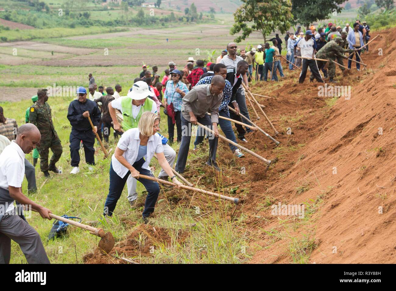"""(181124) -- KAMONYI (RWANDA), Nov. 24, 2018 (Xinhua) -- Foreign diplomats in Rwanda, Rwandan officials and residents participate in monthly community work, Umuganda, in Kamonyi district, central Rwanda, on Nov. 24, 2018. Diplomatic missions in Rwanda and Rwandan Ministry of Foreign Affairs and International Cooperation on Saturday organized a diplomatic Umuganda in Kamonyi. Taking root from Rwandan culture of self-help and cooperation, Umuganda, held on the last Saturday of the month, can be translated as """"coming together in common purpose to achieve an outcome,"""" according to Rwanda Governance Stock Photo"""