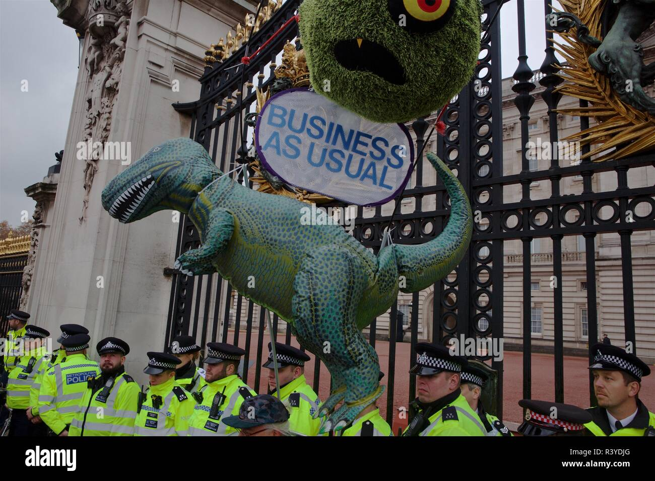 Saturday November 24 2018. Climate change campaign group Extinction Rebellion fly a replica dinosaur outside the gates of Buckingham Palace - London, UK, - Stock Image