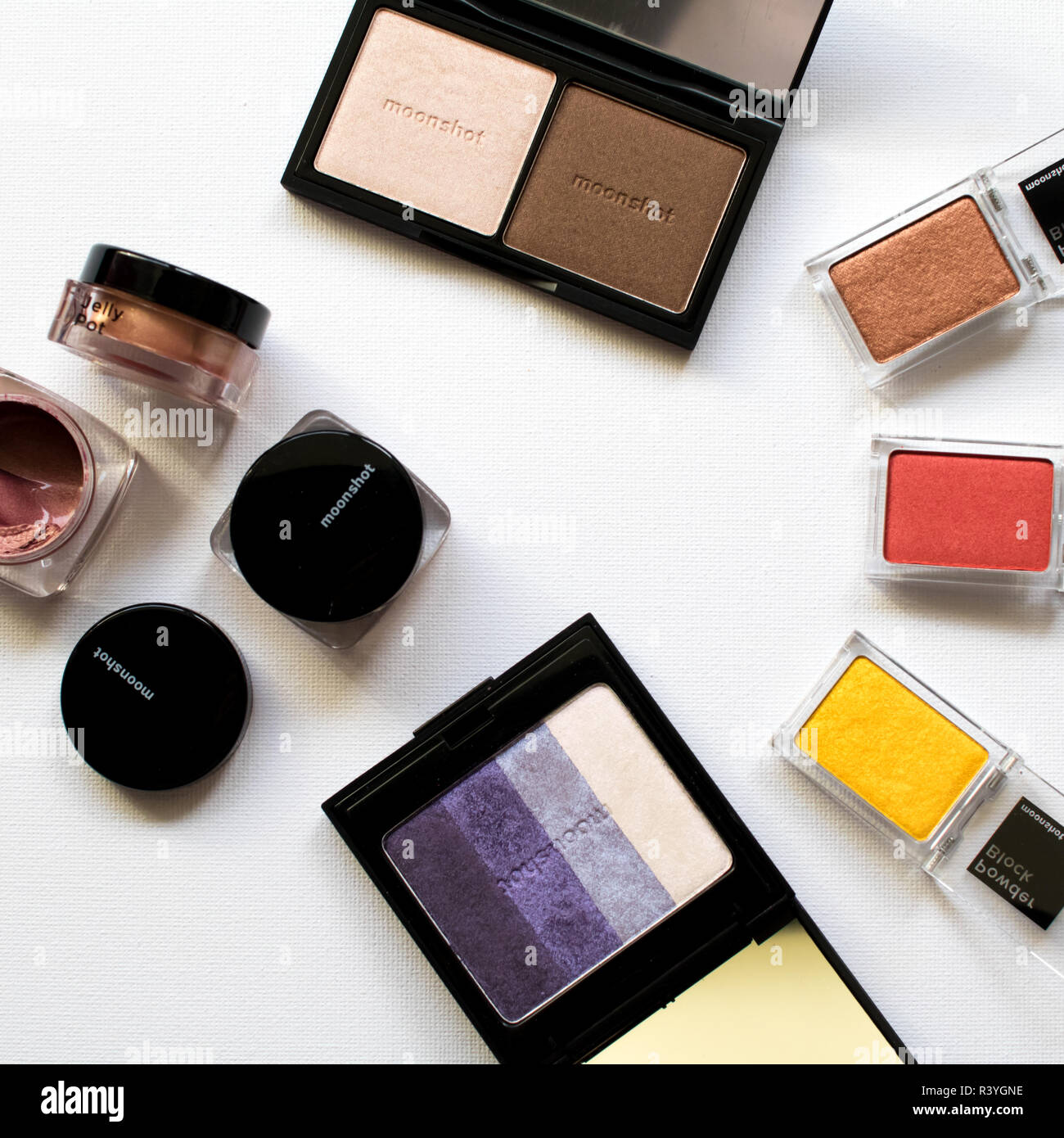 makeup palette purple with bronzer and highlighter and bright eyeshadows red and yellow with gel cream eyeshadows from moonshine. Kbeauty product - Stock Image