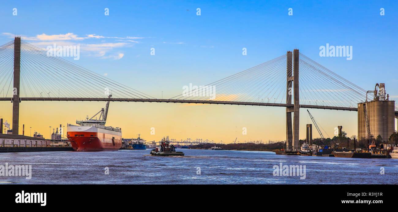 Savannah, Georgia. Tug boat and container ship on Savannah River next to Talmadge Bridge - Stock Image