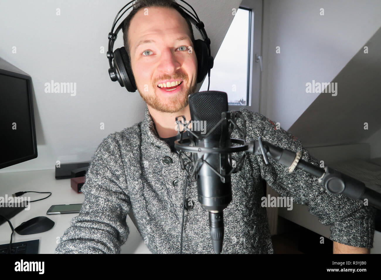 Young male behind condenser microphone radio podcast host voice recording Stock Photo