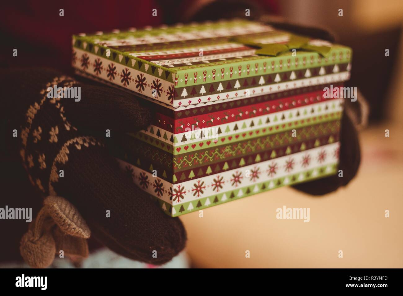In gentle hands on which are wearing warm mittens holding a New Year's box in which a long-awaited gift. The box is decorated with beautiful Christmas - Stock Image