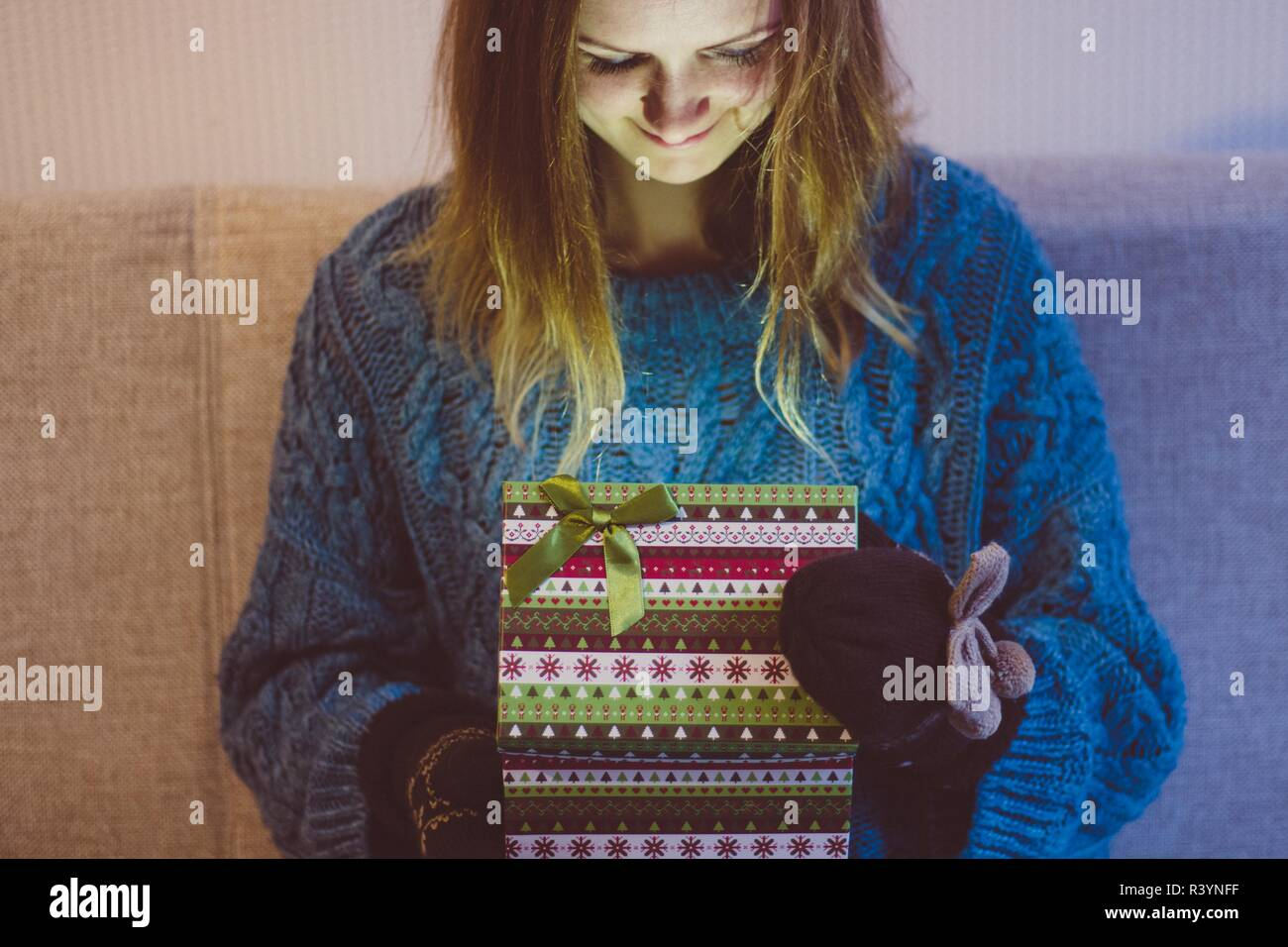 Beautiful and young girl opens a box with modern patterns in which a brightly burning gift. Light falls on her happy face. - Stock Image