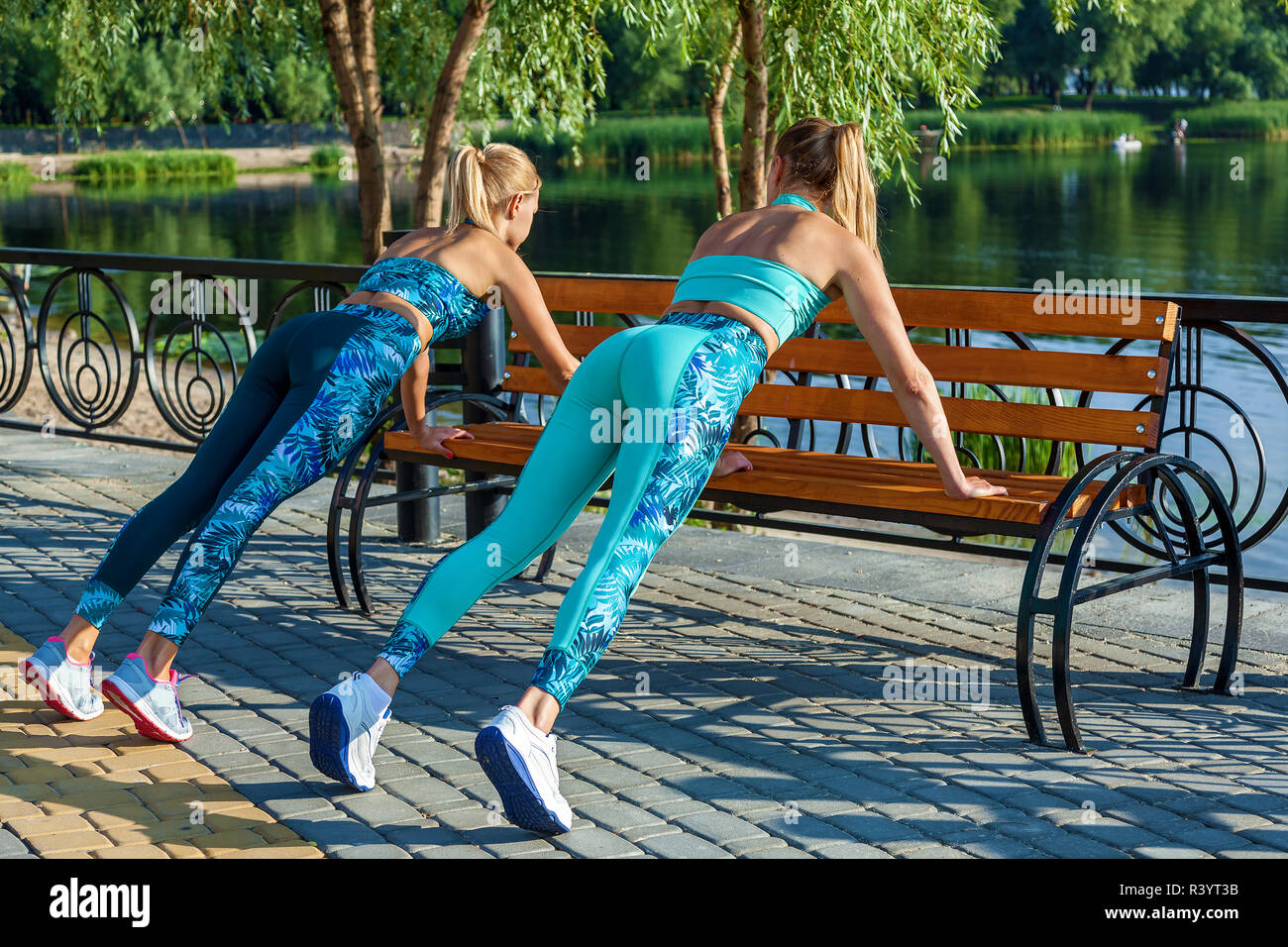 Girls in sports rompers warm up and run. Fitness on the street. Attractive girls doing exercises on the sports field. Sportswear for fitness. Fitness  - Stock Image