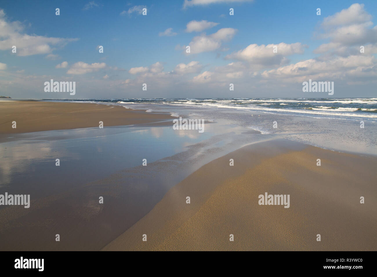 Vast beach at ebb tide, blue sky and white clouds reflected in the water of a gully - Stock Image