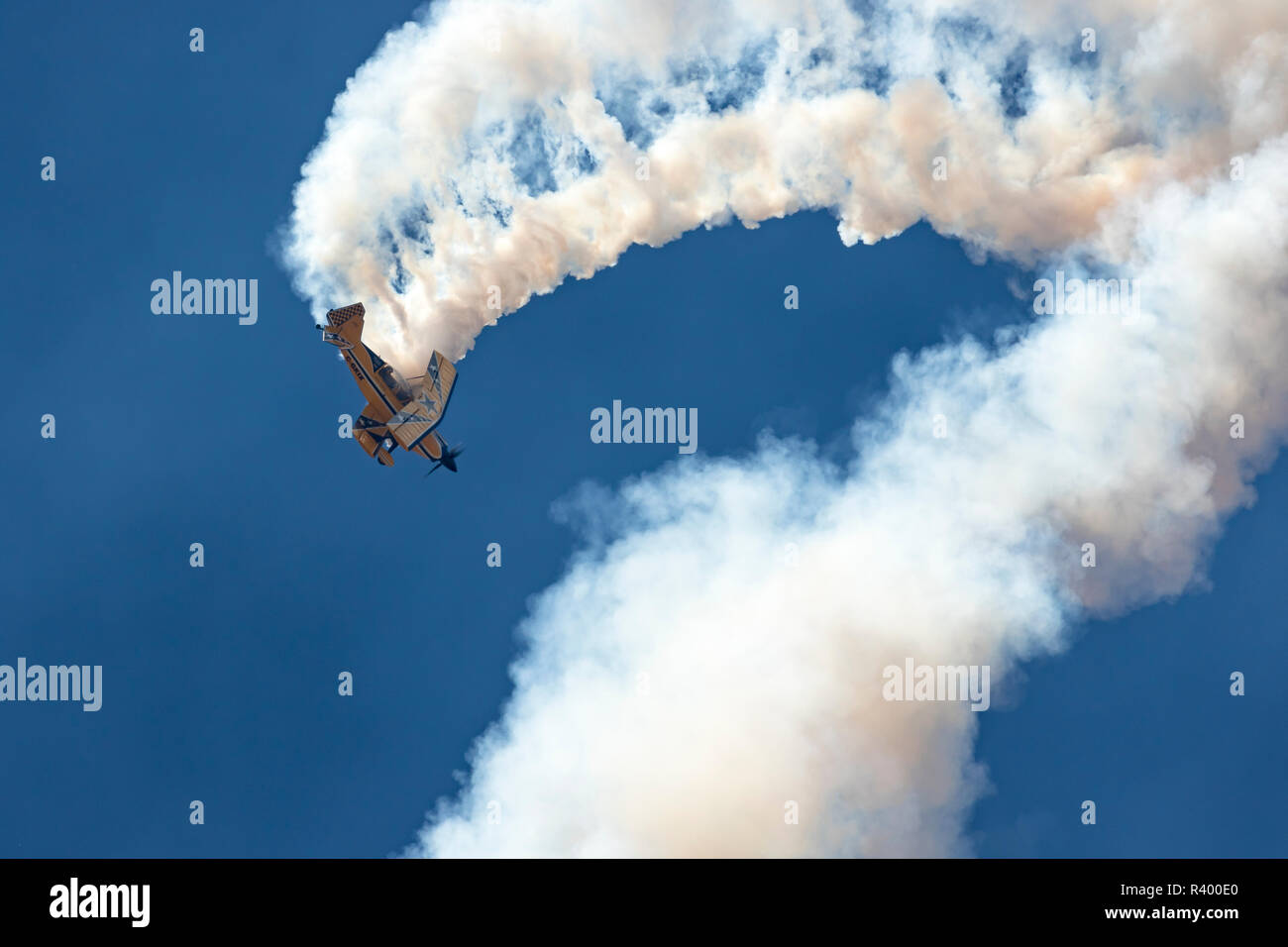 Biplane stunt pilot completes loop while trailing smoke, Madras Airshow, Oregon. - Stock Image